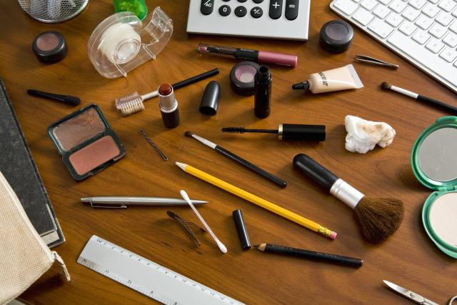 An office desk cluttered with cosmetics and office supplies