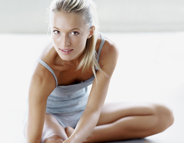 Fit woman doing stretches on yoga mat